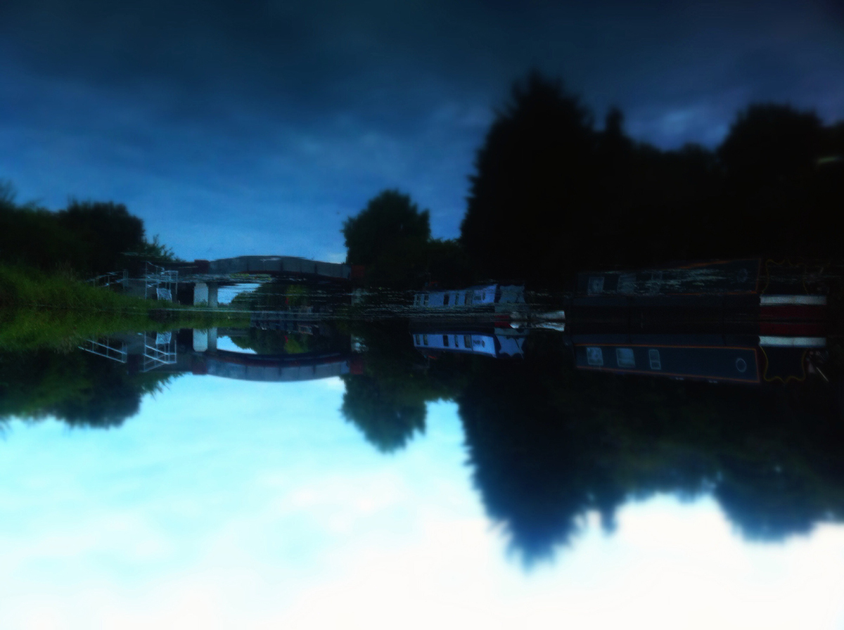 Canal boats reflected in water