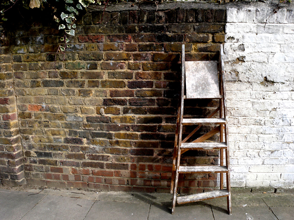 Step ladders against a brick wall