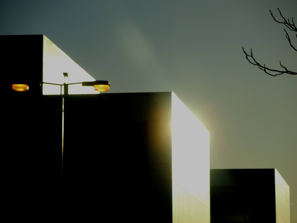 The sun sets over modern architecture.