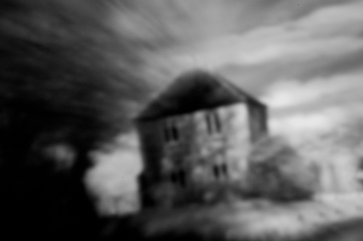 An infrared pinhole lens image of a stone house, captured through the window of a moving car.