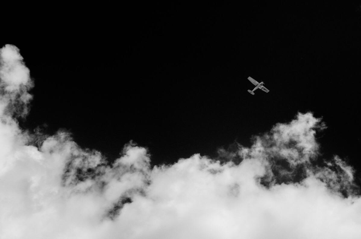 A light aircraft flies low in an infrared sky.