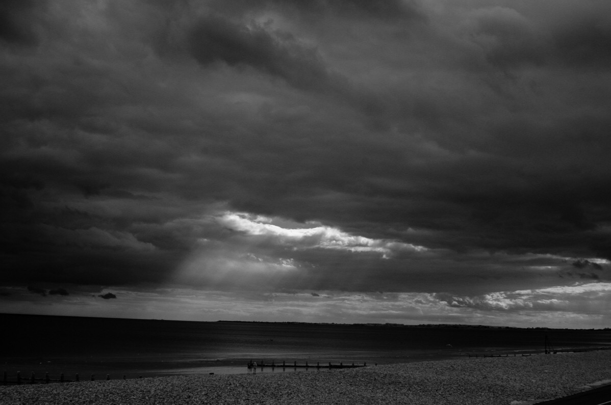 Crepuscular rays, also known as Solstafir, above the sea. Monochrome image.