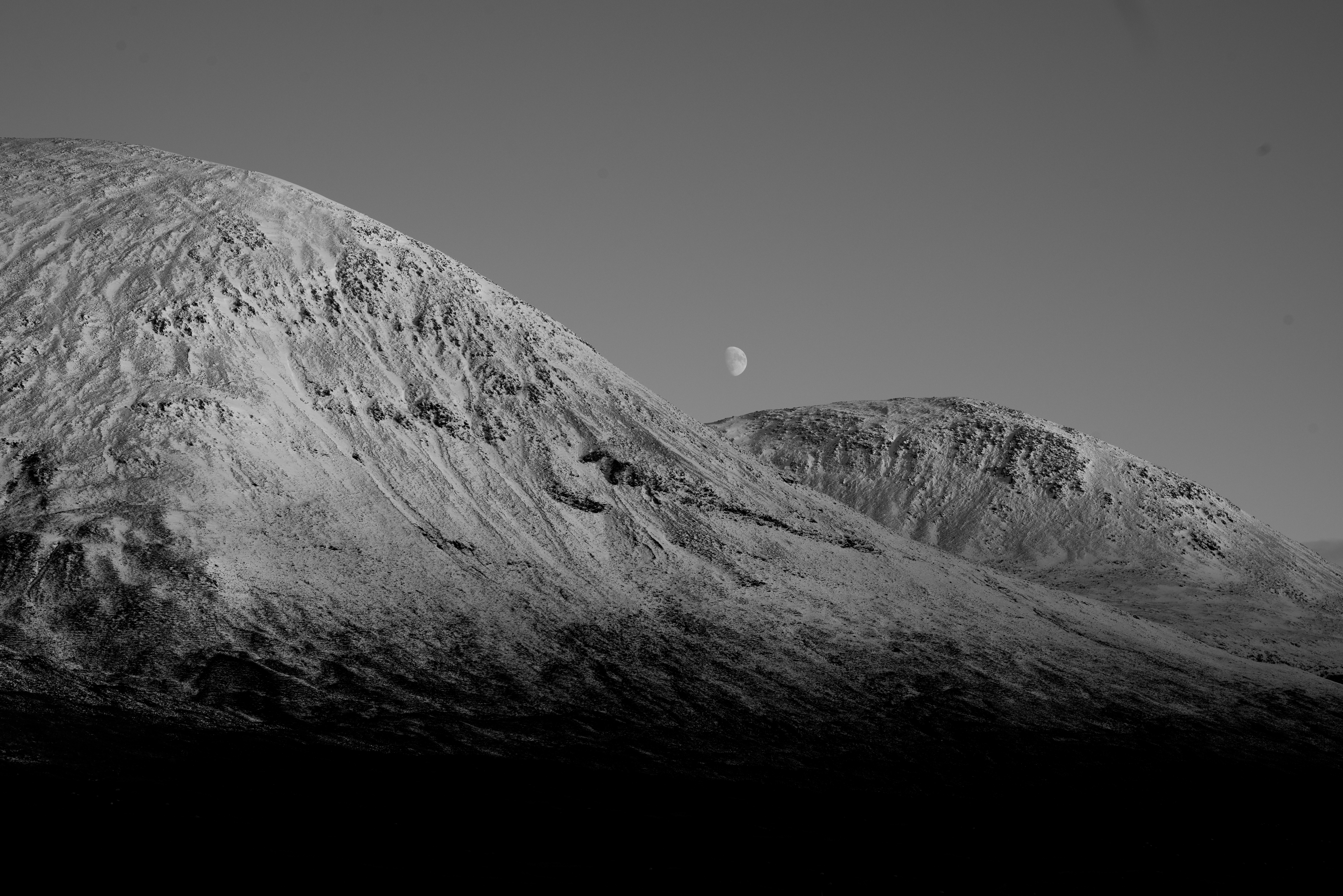 A waxing moon rises over two peaks on The Isle of Skye.