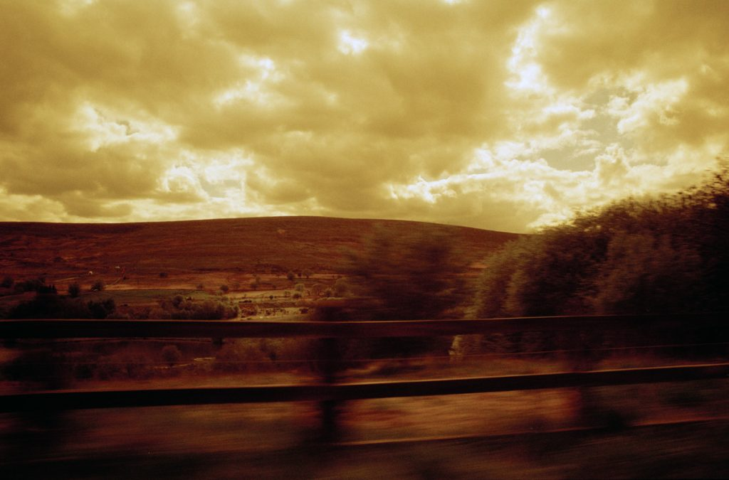 Redscale image of a valley top, taken from a moving car.